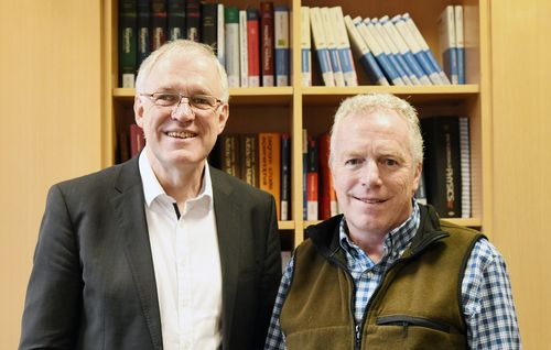 Two men in front of a bookshelf