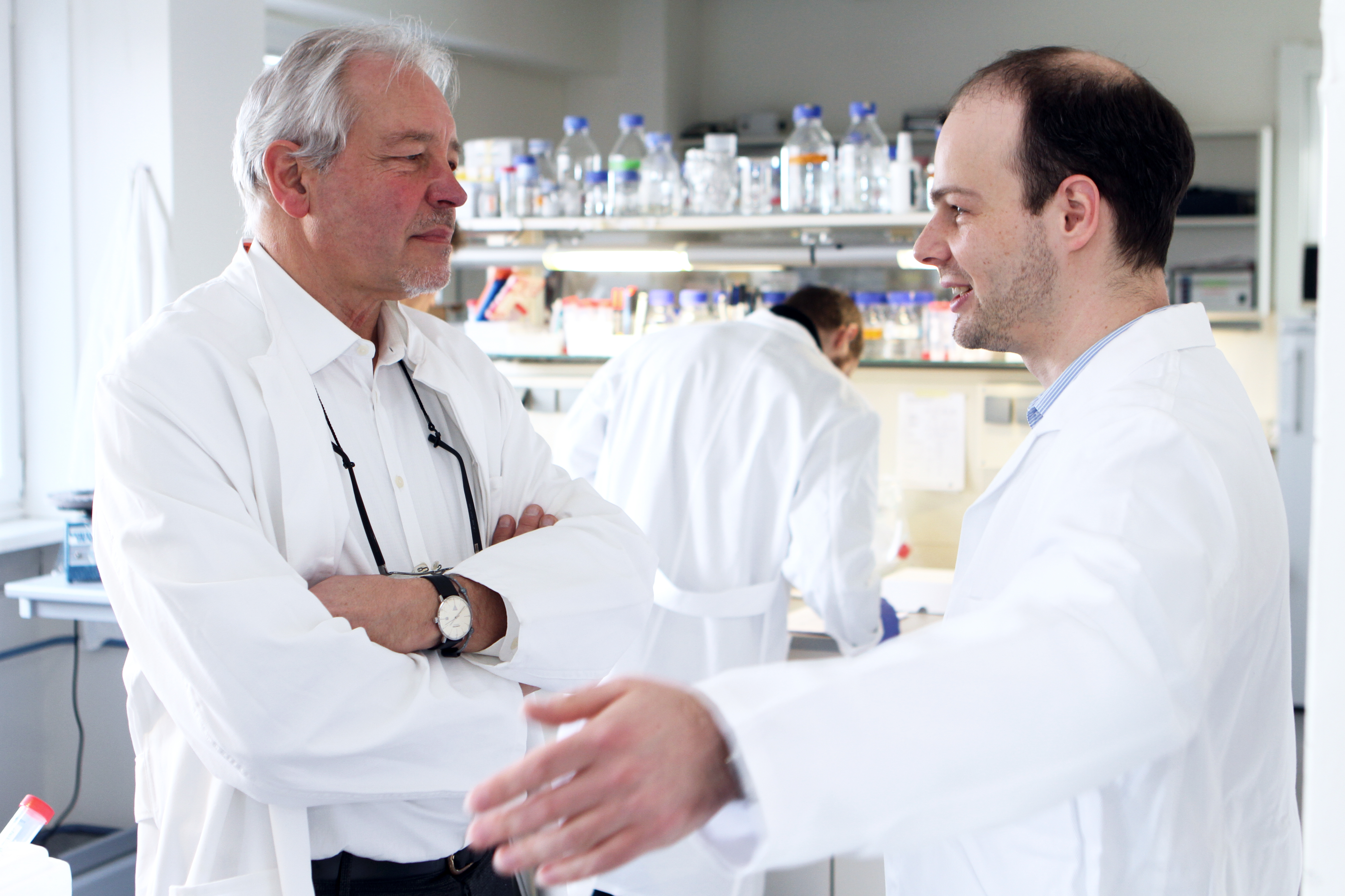 Two scientists talk to each other in a lab