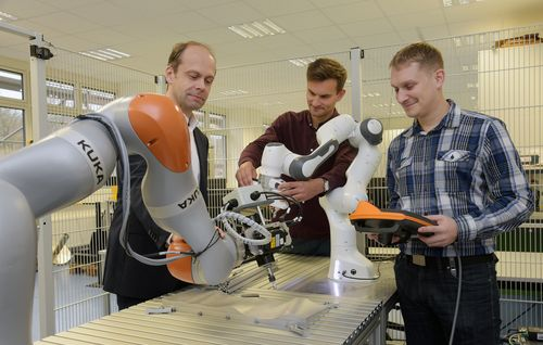Professor and students with robotic arm
