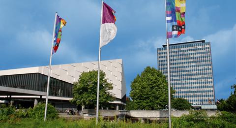 CAU-Flaggen.-Im-Hintergrund-das-Auditorium-Maximum-(links)-und-das-Verwaltungshochhaus-der-Universität
