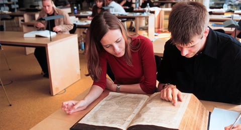 Studierende-mit-einer-Bibel-aus-dem-17.-Jhd.-im-Freihandbereich-der-Universitätsbibliothek.jpg